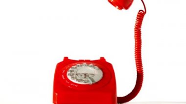 Receiver falling onto red dial phone on white background — Vidéo