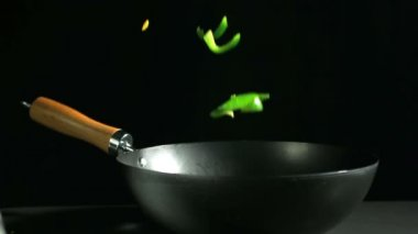Sliced green peppers falling into wok on black background — Stock Video
