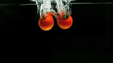 Two tomatoes falling in water — Stock Video