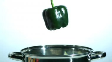 Green pepper falling in saucepan — Stock Video
