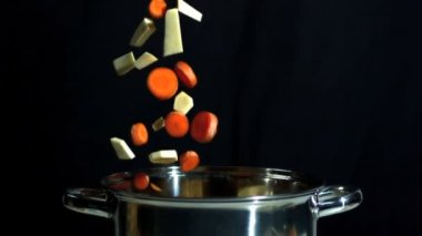 Sliced carrot and parsnip falling into saucepan on black background — Stock Video