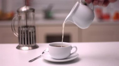 Milk pouring into coffee — Stock Video