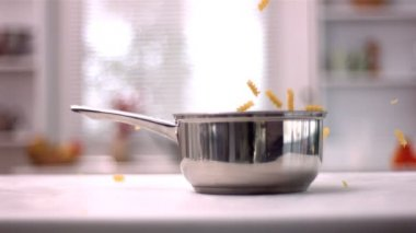 Fusilli falling into a saucepan in kitchen — Stock Video