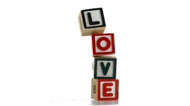 Stacked building blocks spelling out love falling over — Stock Video