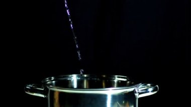 Water flowing into saucepan on black background — Stock Video