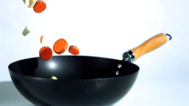Chopped carrots and parsnips falling into wok — Stock Video