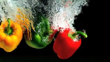 Three peppers falling into water and floating — Stock Video