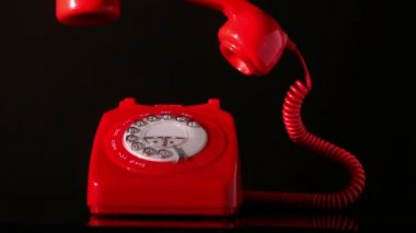 Receiver falling on red dial phone on black background — Vidéo