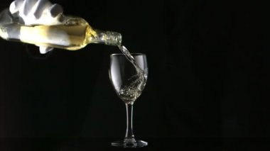 Gloved hand pouring white wine into glass — Stock Video