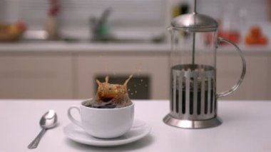 Sugar cube falling into coffee cup in kitchen — Stock Video