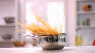 Spaghetti falling in a saucepan in kitchen — Stock Video
