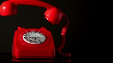 Receiver falling onto red dial phone on black background — Vidéo