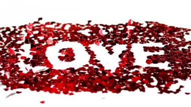 Confetti spelling out love blowing away — Stock Video