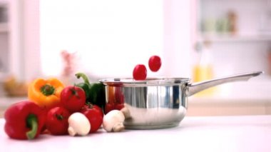 Cherry tomatoes falling in pot in kitchen beside vegetables — Stock Video