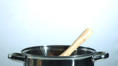 Wooden spoon falling in a saucepan — Stock Video