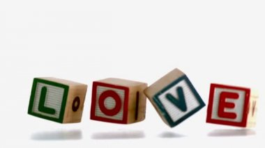 Wooden blocks spelling out love falling — Stock Video