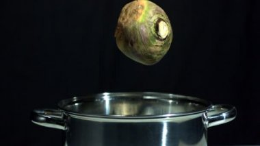 Turnip falling in saucepan on black background — Stock Video
