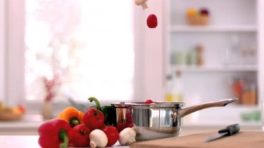 Cherry tomatoes and mushrooms falling in saucepan in kitchen — Stock Video