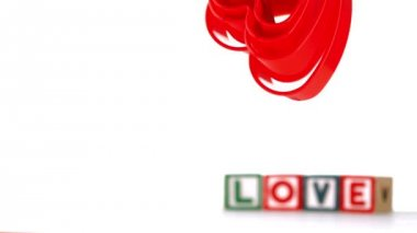 Heart ornaments falling with blocks spelling love in background — Stock Video