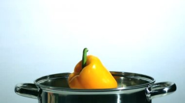 Yellow pepper falling in saucepan — Stock Video