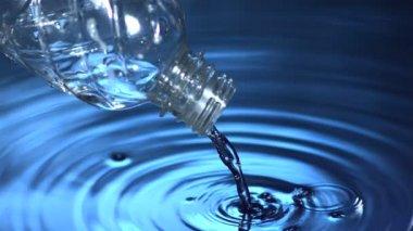 Eau qui coule de la bouteille en plastique dans l'eau bleue — Vidéo