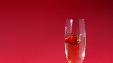 Strawberry falling into champagne flute — Stock Video