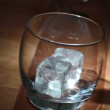 Stock Video: Hand putting ice into tumbler then pouring whiskey