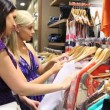 Women looking through clothes rail — Stock Video
