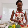 Woman chopping vegetables in kitchen - Stock Photo