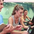 Trainer teaching two women on exercise bikes — Stock Video