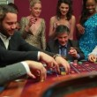 Men placing bets at roulette table watched by women — Stock Video