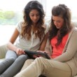 Women sitting on the couch while holding a tablet PC — Stock Video