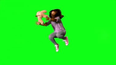 Happy little girl jumping up and catching teddy on green screen — Stock Video