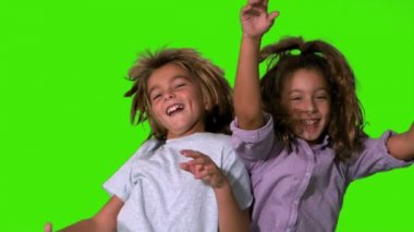 Brother and sister jumping up and crashing on green screen — Stock Video