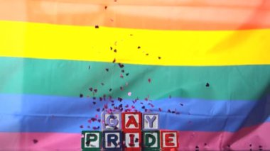 Rainbow flag blowing in the breeze with gay pride blocks and confetti falling — Stock Video