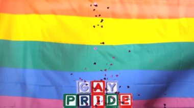 Rainbow flag moving in the breeze with gay pride blocks and confetti falling — Stock Video