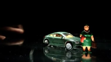 Green toy car hitting a woman figurine — Stock Video