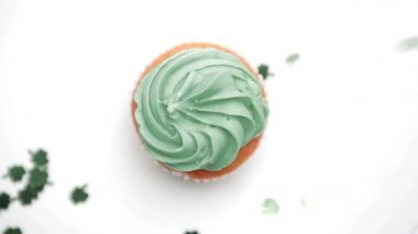 St patricks day cupcake turning with green shamrock confetti falling — Stock Video