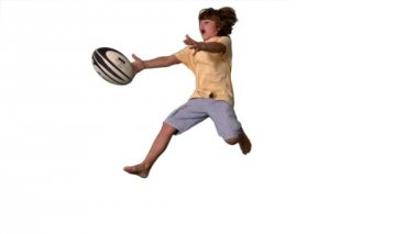 Young boy jumping up and catching a rugby ball on white background — Stock Video