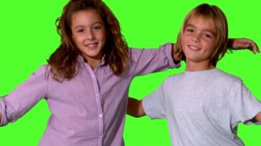 Brother and sister jumping into same shot and embracing on green screen — Stock Video
