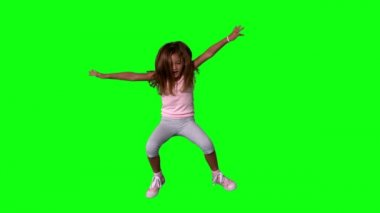 Cute little girl jumping with limbs outstretched on green screen — Stock Video