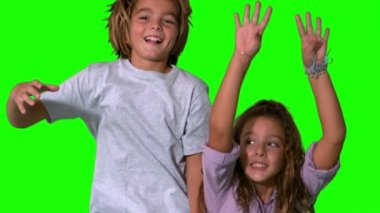 Brother and sister jumping up on green screen — Stock Video