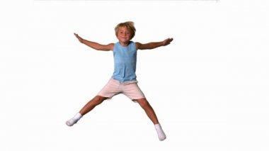Boy jumping with limbs outstretched on white background — Stock Video