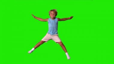 Boy jumping with limbs outstretched on green screen — Stock video
