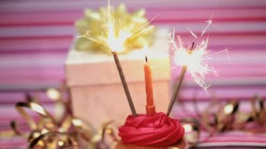 Sparklers on a birthday cupcake with gift — Stock Video