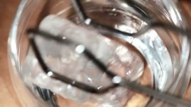 Tongs placing ice into tumbler and whiskey being poured over — Stock Video