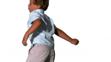 Little boy jumping and turning on white background — Stock Video