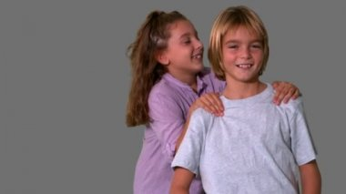 Sister jumping on brothers back on grey background — Stock Video