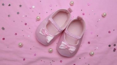 Pink baby booties on pink blanket with pearls — Stock Video