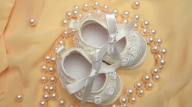 White baby booties with string of pearls — Stock Video